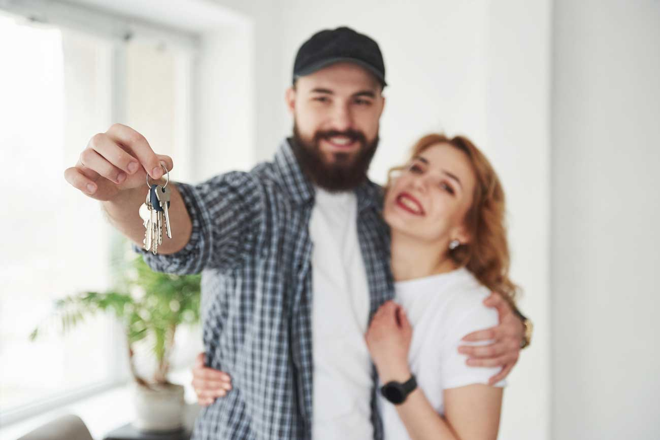 young couple with keys at end of lease